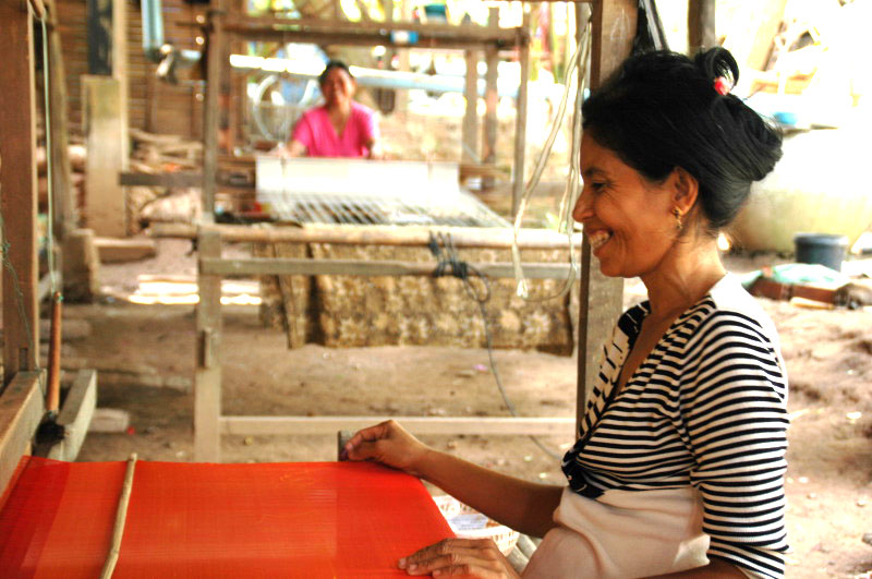 Cambodian artisan is weaving a silk scarf
