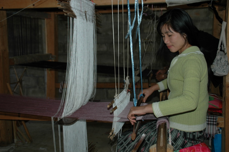 Lao artisan is weaving a complex silk scarf