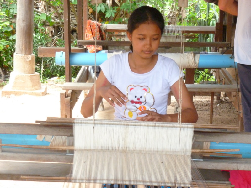 Woman artisan is weaving a silk scarf